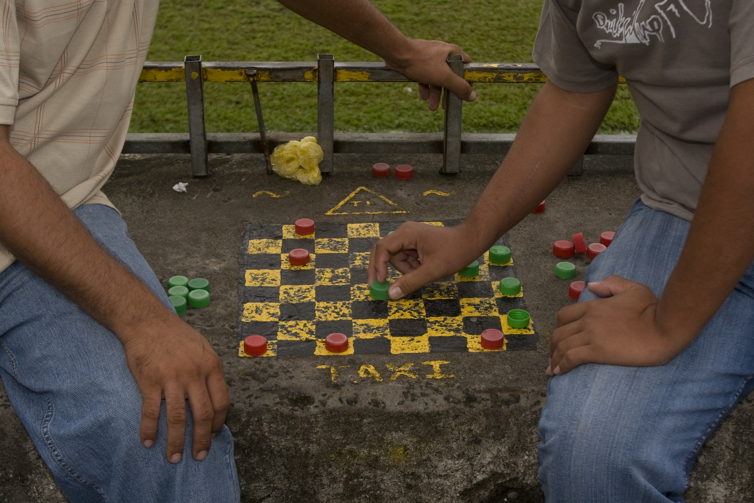 Conductores de Taxi juegan damas chinas en la plaza de Sarapiquí. Taxi drivers play checkers next to the Sarapiquí soccer field.