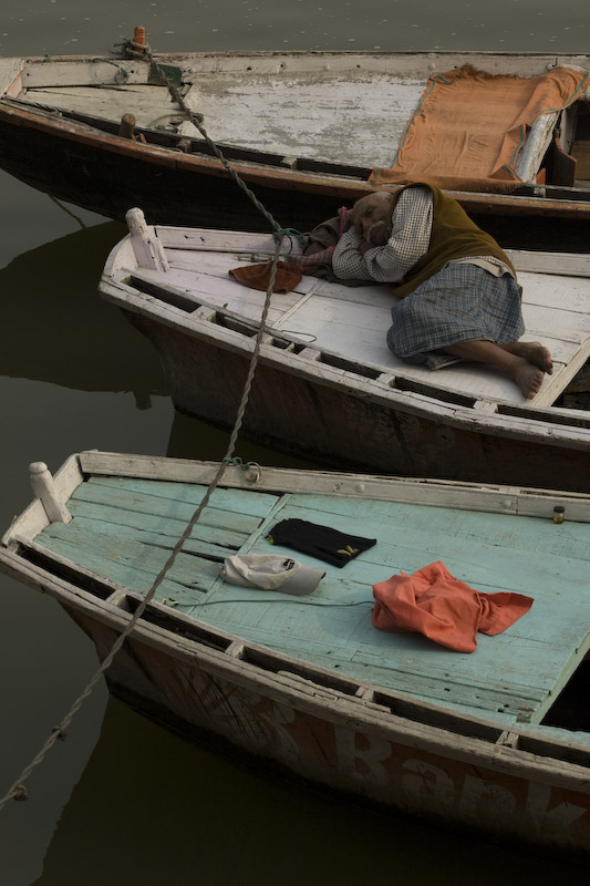 Un hombre descansa en un bote sobre el Río Ganges, Varanassi. A man rests at a boat at the Ganges river, Varanassi.